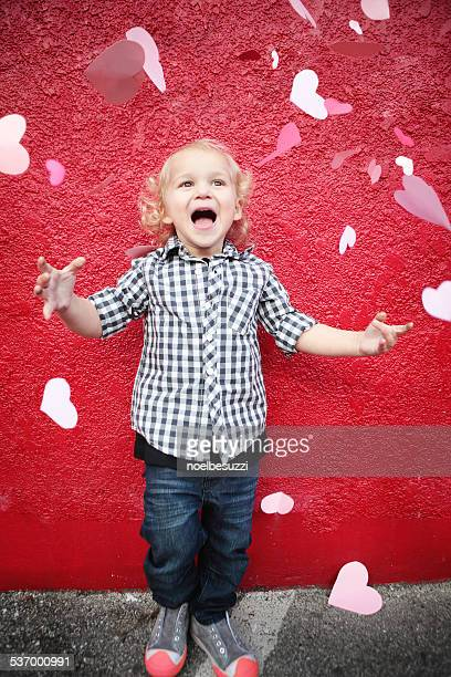 Boy throwing paper hearts in air