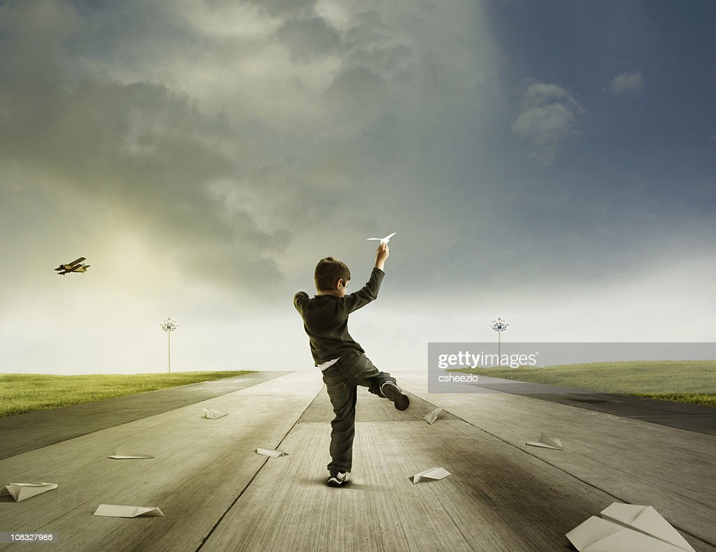 Boy throwing paper planes : Stock Photo