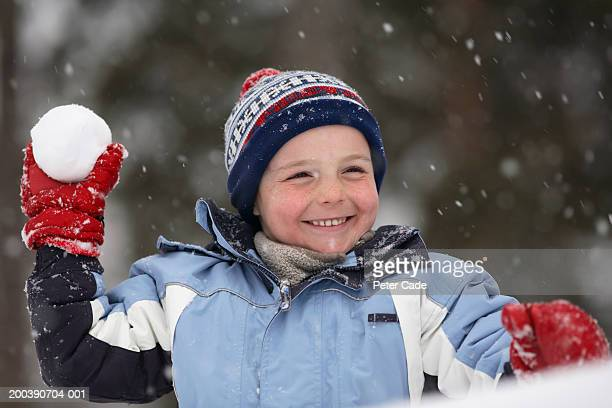 Boy (4-6) throwing snow ball, smiling, close-up