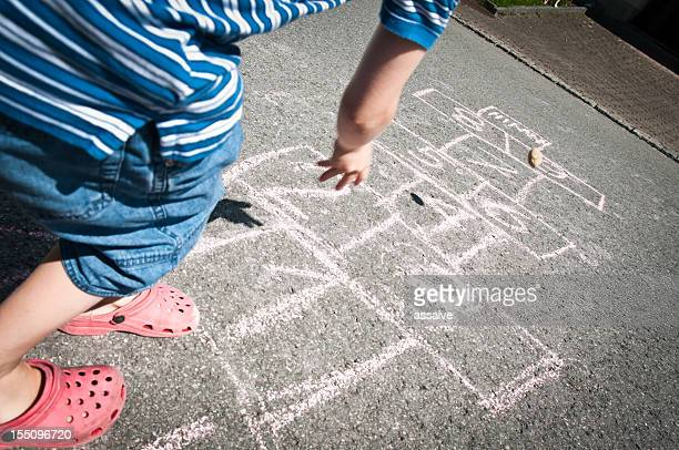 boy throwing stone on hopscotch