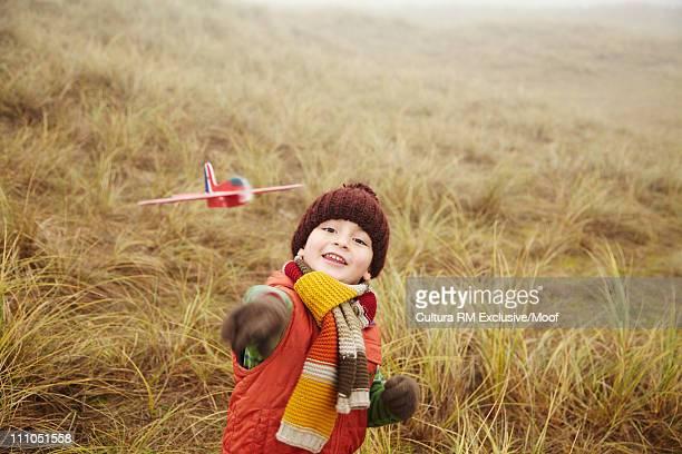 Boy throwing toy aeroplane in field