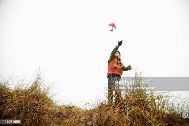 Boy throwing toy aeroplane into the sky