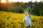 Boy throwing toy airplane in summer day on sunset. Child plays with a toy airplane dreams of journey.