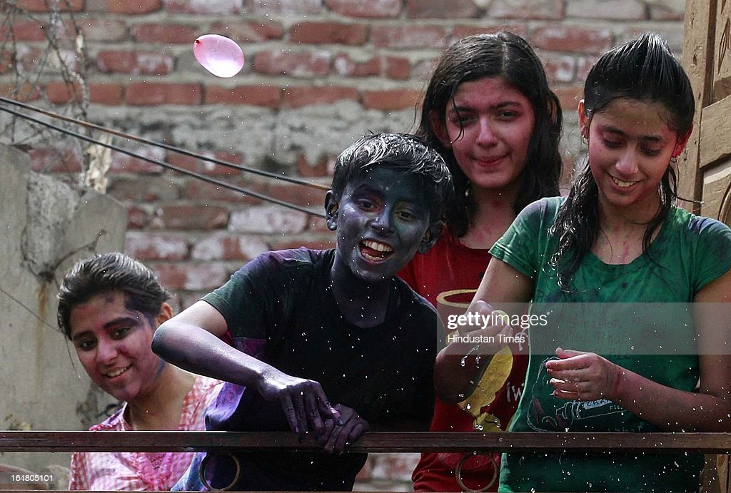 A boy throwing water balloon as children play with colours during the Holi celebration on March 27, 2013 in New Delhi, India. Holi, festival of color is Hindu religious festival also called Basantotsav or spring festival as it mark the arrival of spring. People gather together to play colors, sing and dance to traditional tunes and eat sweets specially Gujiyas.