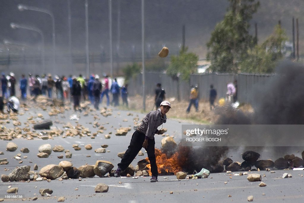A boy throws a rock in the direction of a group of journalists during a farm workers' strike on January 9, 2013 in de Doorns, a small farming town about 140km north of Cape Town, South Africa. Workers on fruit farms have downed tools, demanding a wage hike from 69 rand ($8) to 150 rand ($17.50) a day. The protesters also occupied part of the country's major N1 highway, forcing dozens of police officers and two armoured vehicles to move down the road, pushing the protesters back from the town entrance.