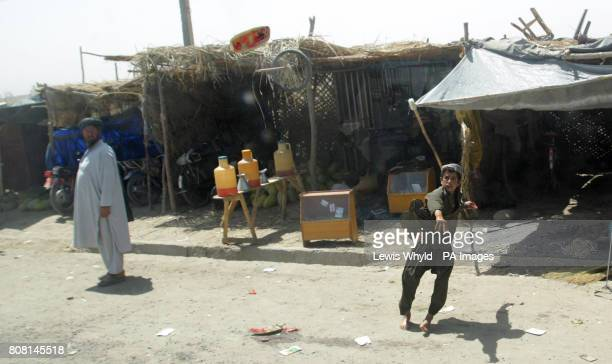 A boy throws a watermelon at an armoured vehicle carrying British troops in Nade Ali in Helmand Province Afghanistan