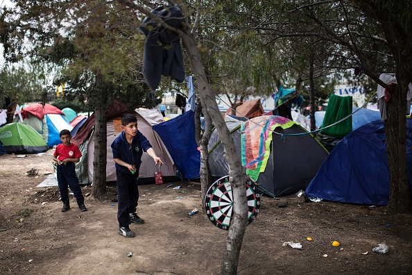 TOPSHOT - A boy throws darts outside a passenger terminal used as a shelter for refugees and migrants at the Piraeus harbour in Athens on April 3, 2016. Greek and EU authorities fine-tuned an opera...