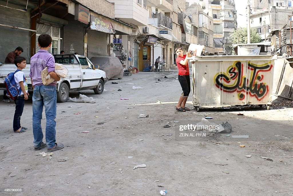 A boy throws rubbish into a container on which Jumaa, an artist of the so-called 'Funny Media Activist' group, sprayed a graffiti reading in Arabic 'We throw you away', on June 2, 2014 in the northern Syrian city of Aleppo. The group aims to paint dumpsters all over Aleppo's rebel-held areas before the elections. 'Cast your vote here,' Jumaa, sprayed on the metal containers in large, brightly coloured letters, transforming some of them into mock ballot-boxes.