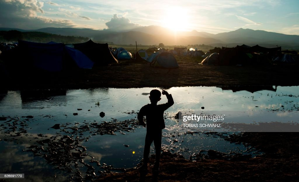 A boy throws stones into a puddle at a makeshift camp for migrants and refugees near the village of Idomeni not far from the Greek-Macedonian border on April 30, 2016. Some 54,000 people, many of them fleeing the war in Syria, have been stranded on Greek territory since the closure of the migrant route through the Balkans in February. / AFP / TOBIAS