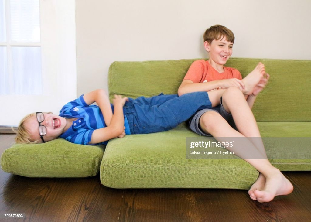 Boy Tickling Brother Feet On Sofa At Home Stock Photo