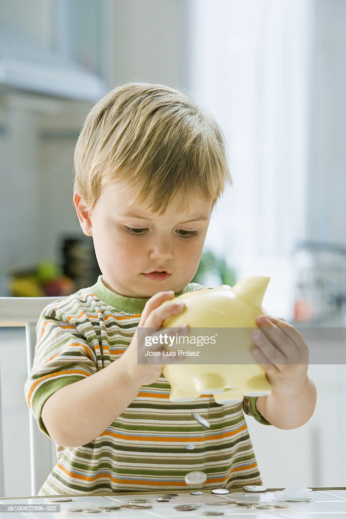 Boy (3-4) tipping coins from piggy bank : Stock Photo