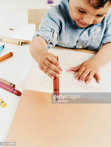 Boy Toddler Sitting Colouring With Crayons