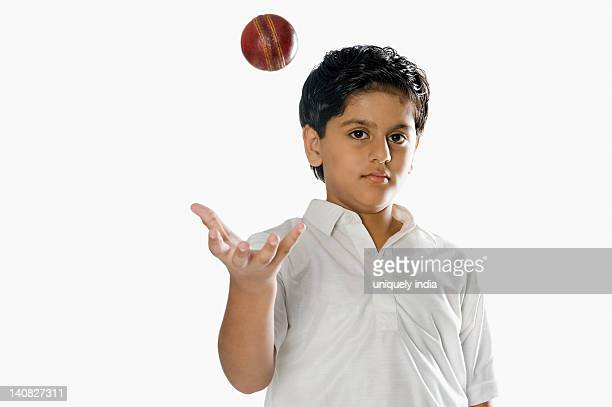 Boy tossing a cricket ball