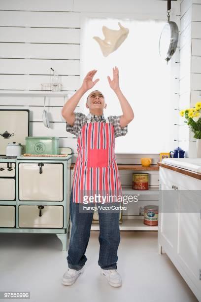 Boy tossing pizza dough