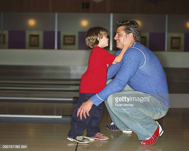Boy (2-4) touching father's face in bowling alley, side view