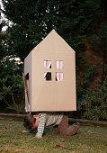 Boy (6-7) transporting cardboard house on cart