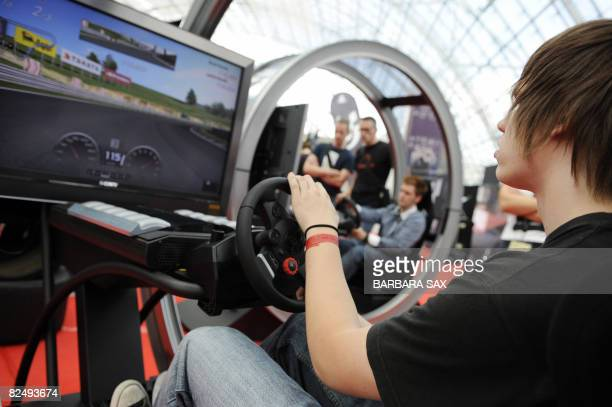 A boy tries out a playstation Gran Turismo driving simulator at the GC fair for computer games and entertainment on August 21 the first day open to...