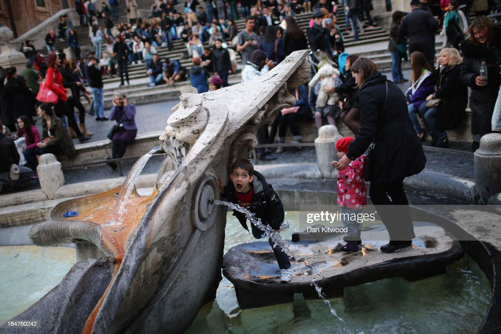 A boy tries to get a mouthfull of water in the fountain at the foot of the Spanish Steps on March 27, 2013 in Rome, Italy.
