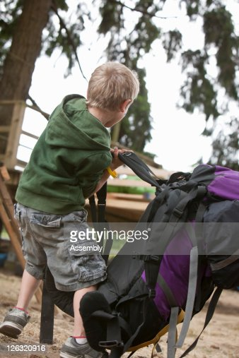 Boy tries to put on large backpack in the woods : Stock Photo