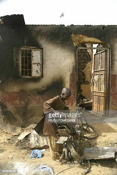 A boy tries to remove a burnt motorcycle lying in front of a burnt building at Shekarar Maiyaki Sharada industrial estate in Kano 14 May 2004 where...