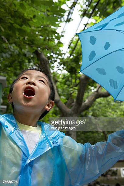 A boy trying to catch a raindrop in his mouth.