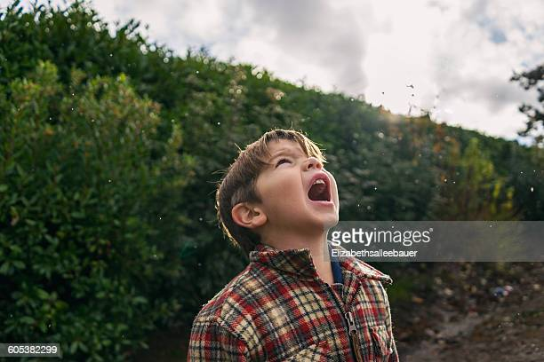 Boy trying to catch raindrops in his mouth