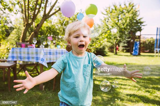 Boy trying to catch soap bubbles in garden