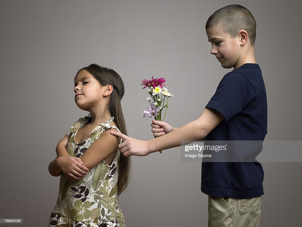 Boy trying to give flowers to girl : Stock Photo