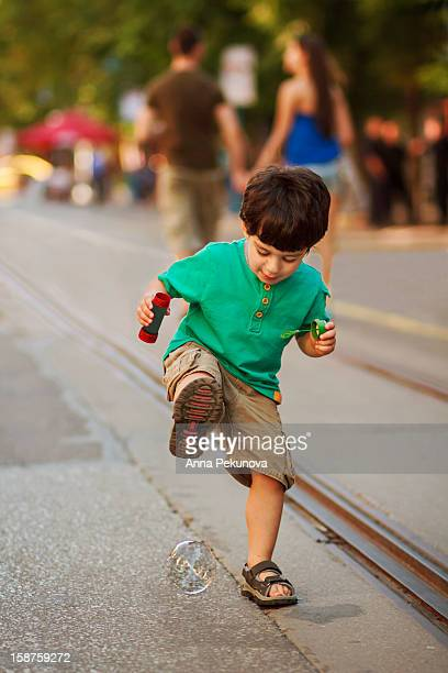 Boy trying to trample soap bubble