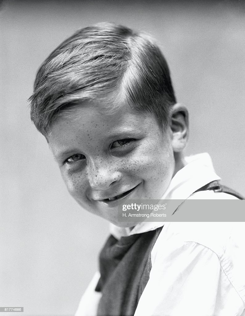 Boy turning head to side, smiling, portrait. : Stock Photo