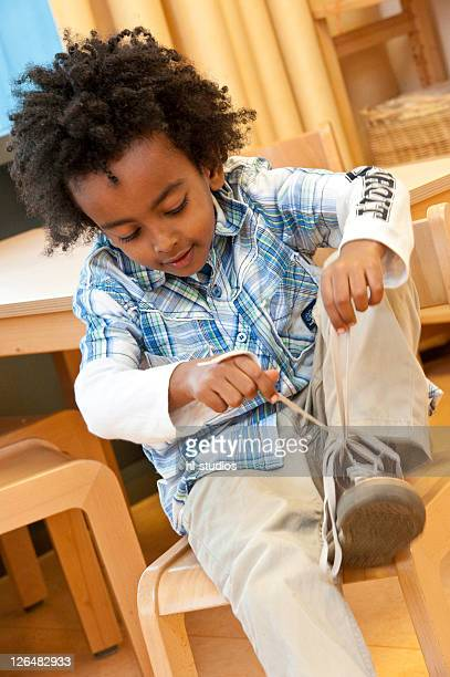 Boy tying his shoelace