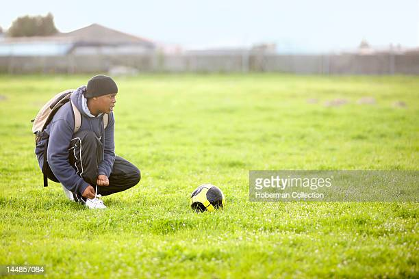 Boy tying shoelace next to soccer ball