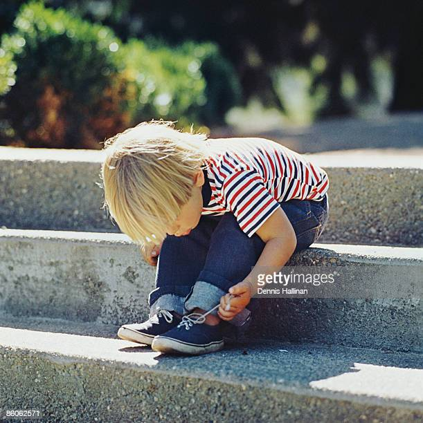 Boy tying shoelaces