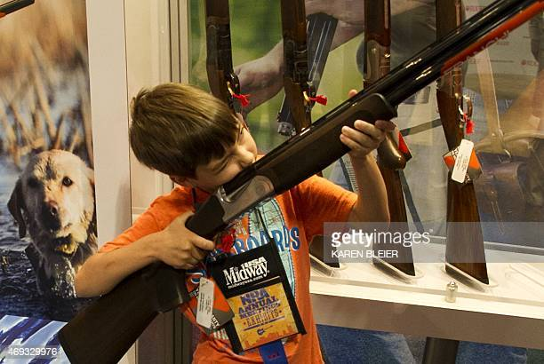 A boy under his parents' supervision aims a shotgun April 11 2015 at the 2015 NRA Annual Convention in Nashville Tennessee AFP PHOTO / KAREN BLEIER