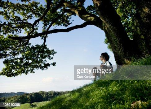 boy under tree in landscape : Photo