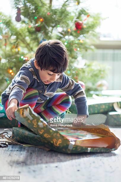 Boy unpacking Christmas present