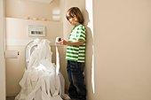 Boy unrolling toilet paper into toilet