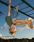 Boy upside down on monkey bars