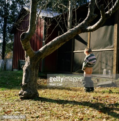 Boy (4-6) urinating in yard, rear view