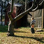 Boy (4-6) urinating in yard, rear view