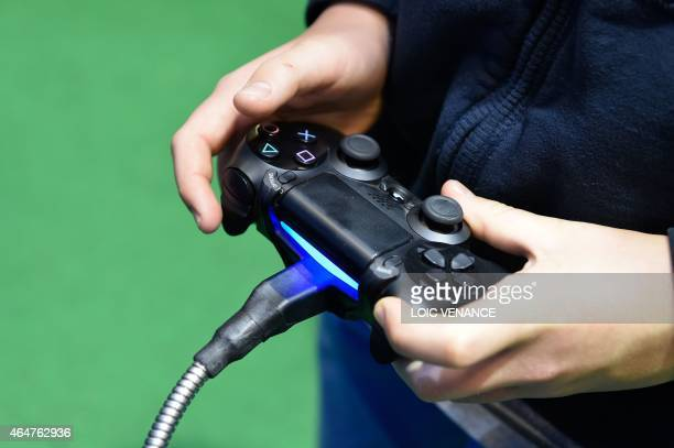 A boy uses a joystick to play a farming simulation video game during the Paris international agricultural fair at the Porte de Versailles exhibition...
