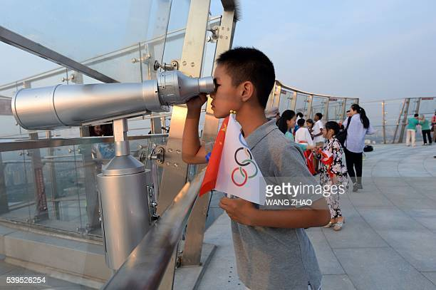 A boy uses a telescope on the top of the Beijing Olympic Tower in Beijing on June 12 2016 / AFP / WANG ZHAO