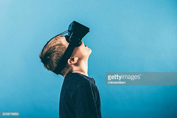 Boy uses VR glasses and looks up