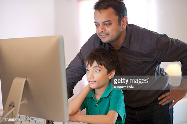 Boy using a desktop pc with her father
