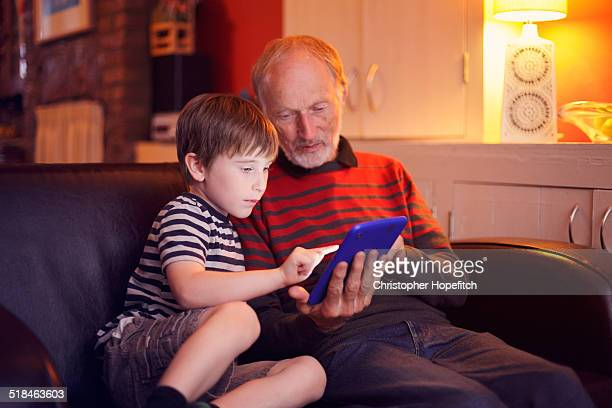 Boy using a tablet computer with Grandad
