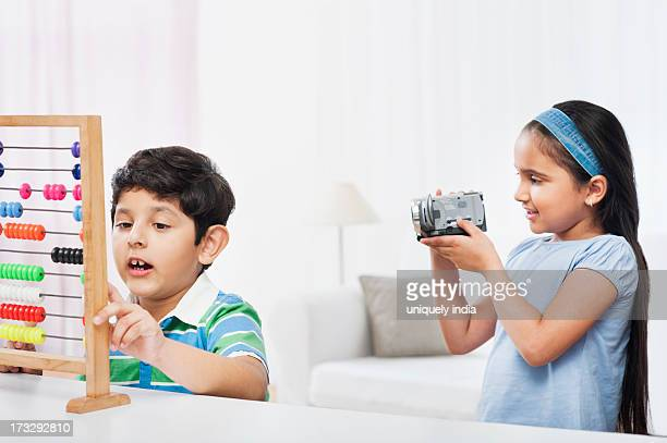 Boy using an abacus and his sister filming him with a video camera