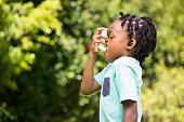 Boy using an asthma inhaler in the park