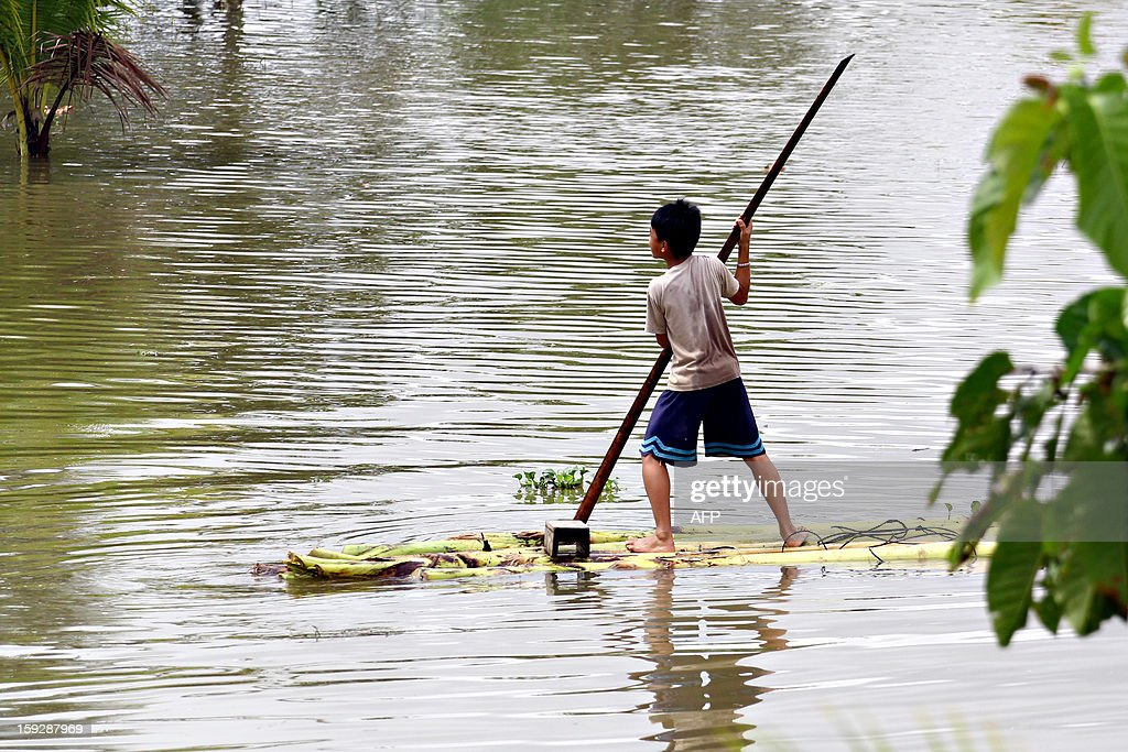 A boy using an improvised raft made from banana trees, rows along a flooded village caused by heavy rains in Butuan City, Agusan del sur province, in the southern island of Mindanao on January 11, 2013. Flooding caused by heavy rains in the country's south has led 5,000 people to flee riverside homes, though no casualties reported so far. AFP PHOTO/Erwin Mascarinas