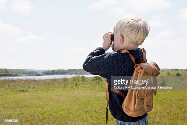 Boy using binoculars in grassy field