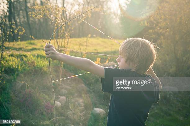 Boy using bow self-built of twigs and looms